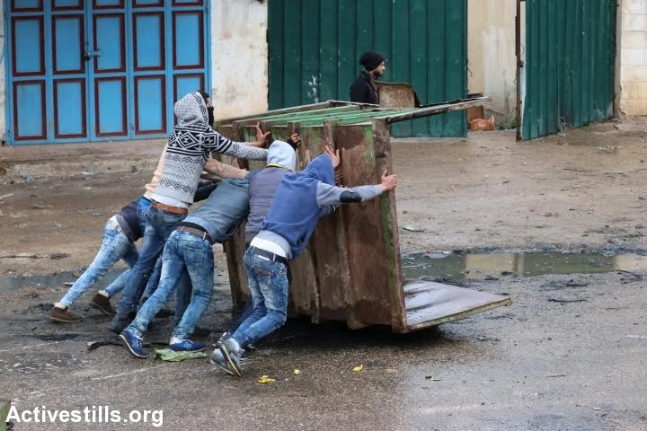 Palestinians take cover during clashes with Israeli forces in Qabatiya, West Bank, February 6, 2016. (photo: Ahmad al-Bazz/Activestills.org)