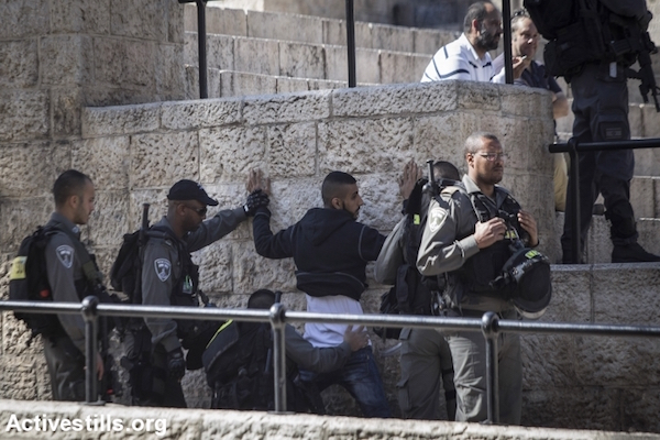 Israeli Border Police officers stop and frisk a young Palestinian man at the Damascus Gate to the Old City of Jerusalem, February 16, 2016. (Faiz Abu Rmeleh/Activestills.org)
