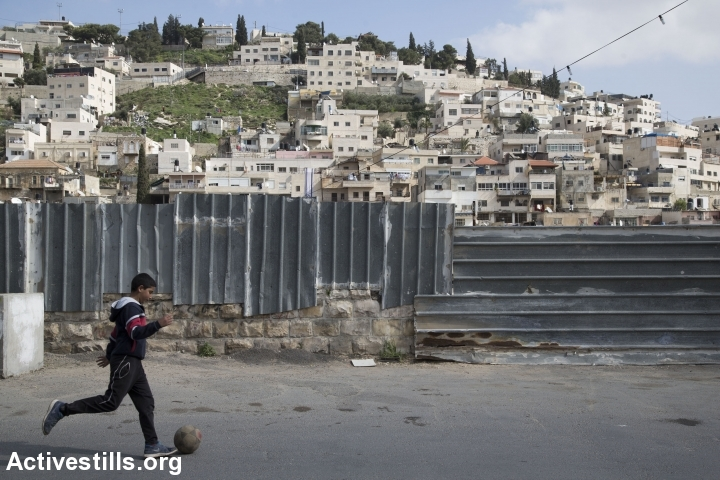 A Palestinian child plays next to a wall in the East Jerusalem neighborhood of Silwan, February 21, 2016. (Activestills.org)
