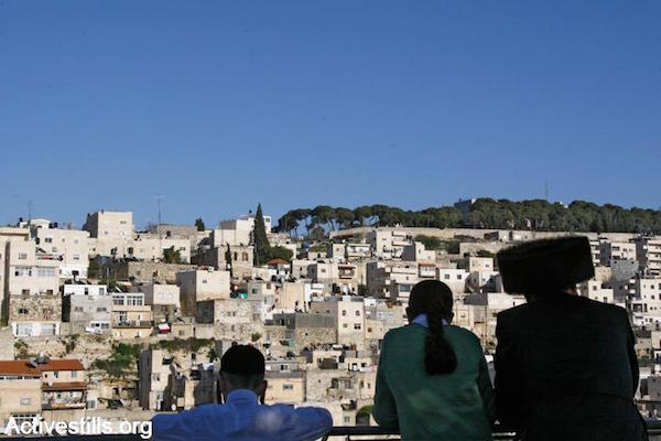 Orthodox Jews look out over the Palestinian village of Silwan in East Jerusalem. (Yotam Ronen/Activestills.org)
