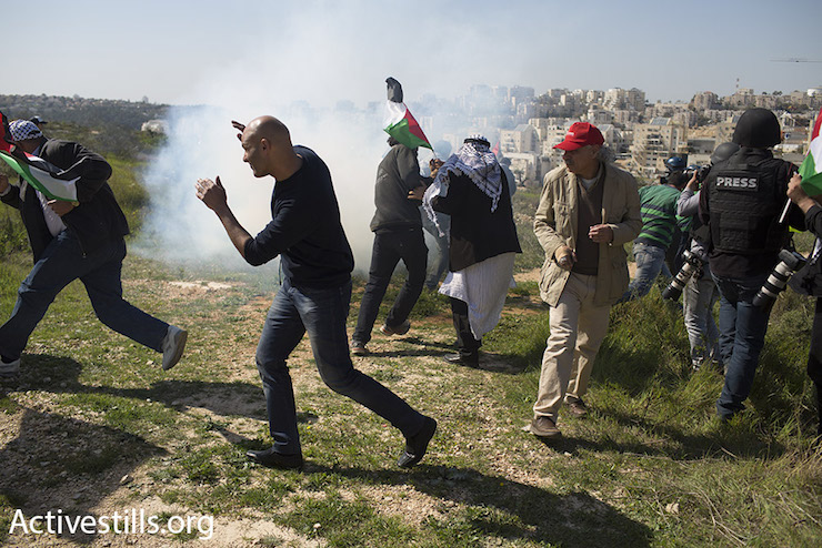 Protesters scatter as Israeli troops use stun grenades to disperse a nonviolent protest in the West Bank village of Bil'in, February 19, 2016. (Oren Ziv/Activestills.org)