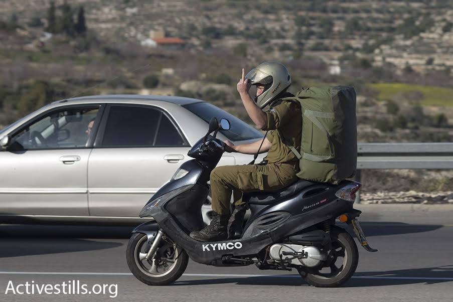 An Israeli soldier flips off Israeli and Palestinian demonstrators during a protest march in the West Bank, February 5, 2016. (photo: Oren Ziv/Activestills.org)