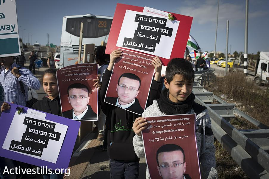 Palestinians and Israelis hold up posters of Muhammad al-Qiq, a Palestinian journalist on hunger strike in an Israeli hospital, during a joint protest at the 'tunnels checkpoint,' south of Jerusalem, February 5. 2016. (photo: Oren Ziv/Activestills.org)