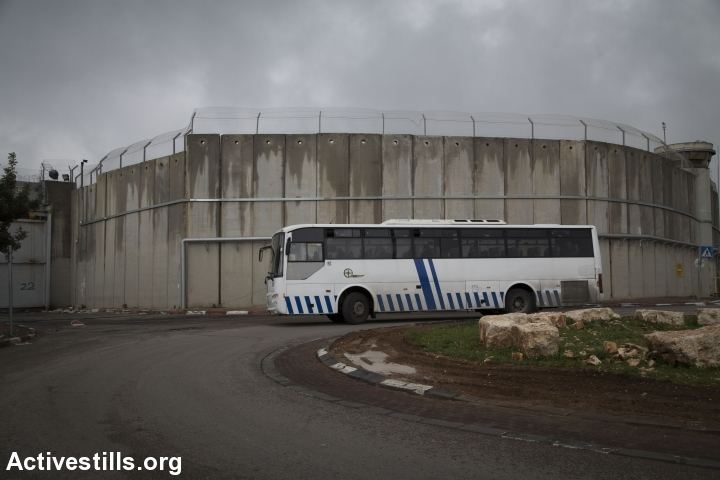 A Palestinian bus drives along Israel's separation wall between Jerusalem and the West Bank city of Jerusalem, February 23, 2016. (Oren Ziv/Activestills.org)
