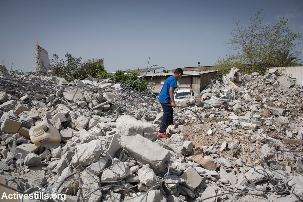 A child plays in the rubble of three homes that Israeli authorities demolished a few hours earlier in the unrecognized village of Dahmash, April 15, 2015. (Activestills.org)