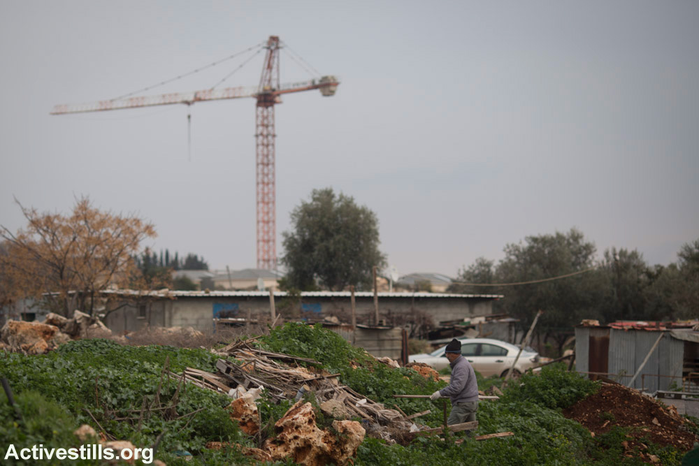 A crane at a construction site for a new Jewish neighborhood in Karmiel looms over homes in the unrecognized village of Ramiya. (Oren Ziv/Activestills.org)