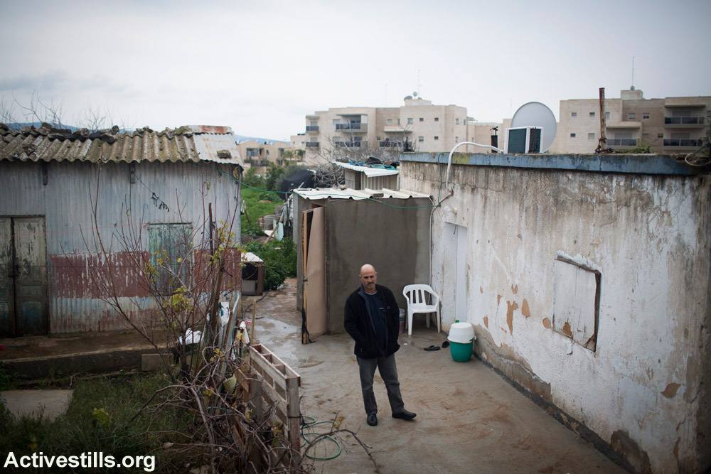 Sales, son of Abu Saleh, stands in between homes in the unrecognized village of Ramiya. New luxury apartments in the city of Karmiel, just a few hundred meters away, are visible in the background. (Oren Ziv/Activestills.org)