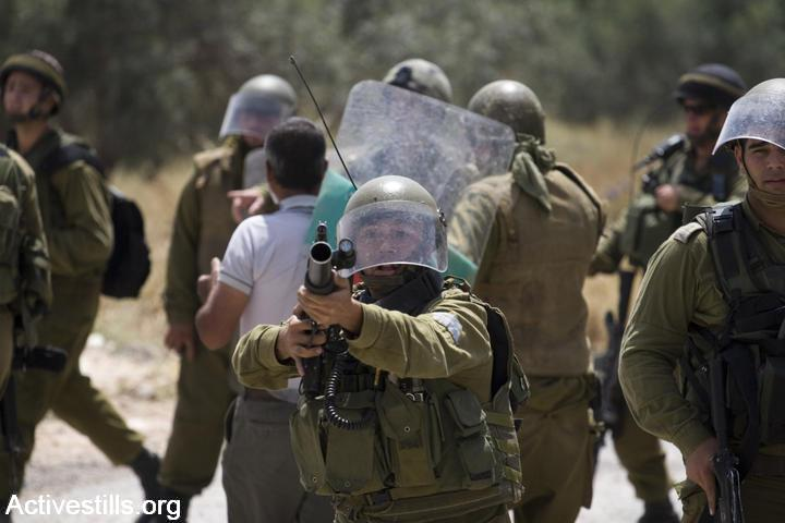An Israeli soldier aims his gun at protesters during a weekly demonstration against the Israeli Separation Wall in Bil'in, West Bank, May 7, 2010. (photo: Oren Ziv/Activestills.org)