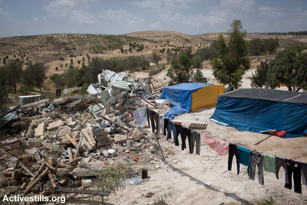 Laundry hangs in front of the rubble of several homes and animal shelters demolished by Israeli authorities in the unrecognized village of Atir, May 21, 2013. The Jewish National Fund plans to expand a forest called 'Yatir,' seen in the background, on the village's land. (Activestills.org)