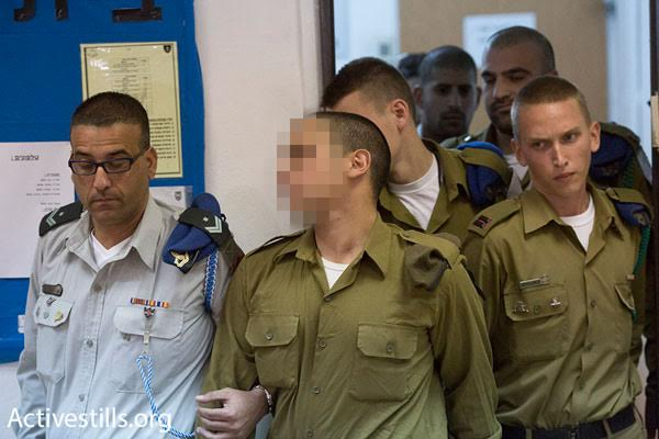 The soldier accused of shooting killing an unarmed, incapacitated Palestinian man is led into court military court, Kiryat Malachi, March 29, 2016. (photo: Oren Ziv/Activestills.org)