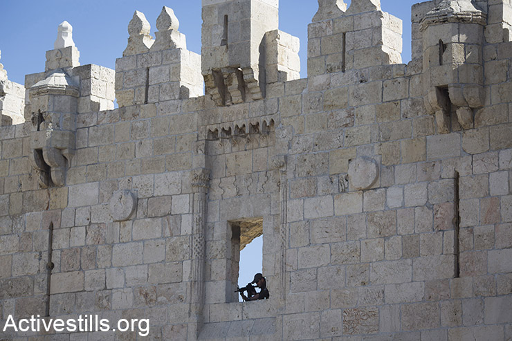 An Israeli anti-riot police sniper is posted on a wall above Damascus Gate in Jerusalem's Old City, February 17, 2016. (Activestills.org)