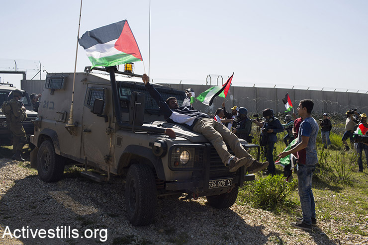 A demonstrator sits on top of a Israeli army jeep during a protest protest marking 11 years to the struggle against the separation wall in Bil'in, February 19, 2016. (Activestills.org)