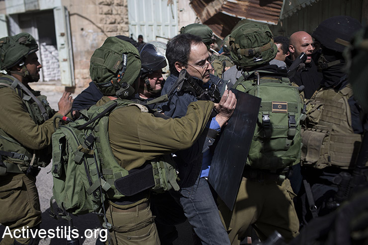 Israeli soldiers arrest activist Gadi Algazi during a protest against the closure of Shuhada Street to Palestinians in the West Bank city of Hebron, February 21, 2014. The army arrested 12 Israeli activists as some 150 protesters gathered to mark the 22nd anniversary of the street's closure following the Ibrahimi Mosque Massacre in 1994 (Activestills.org) For more photos from the demo, click here.