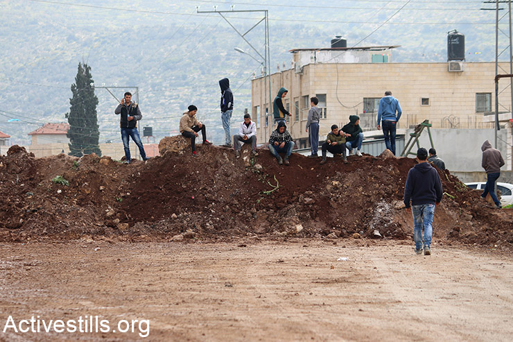 Palestinian youth sit on dirt mounds created by Israeli military bulldozers to block the main entrance to Qabatiya, near Jenin, West Bank, February 23, 2016. (Activestills.org)
