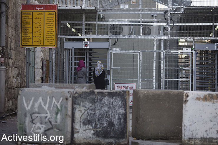 Palestinians walk towards a checkpoint to cross over into Shuhada Street in the H2 area of Hebron, West Bank, February 24, 2016. (Activestills.org)