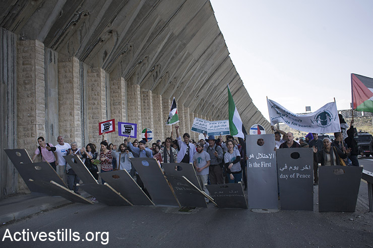 Activists hold up a mock separation wall during a protest against the occupation on the West Bank's main Jerusalem-Hebron highway, Beit Jala, West Bank, February 5, 2016. (Activestills.org)