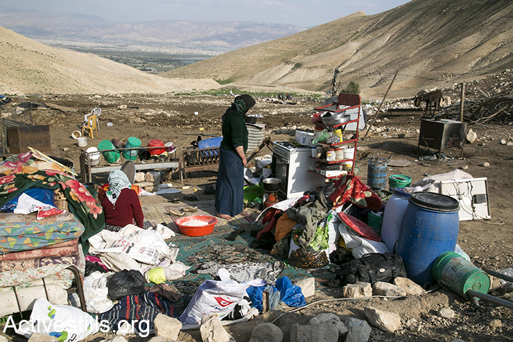 A woman from the small community of Ein Kurzliya in Jordan valley, West Bank prepares bread next to her belongings, following a demolition of houses and animal shelters in the area, February 10, 2016. (Activestills.org)