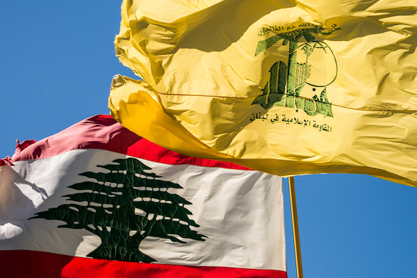 A Lebanese and Hezbollah flag fly side by side. (Illustrative photo by John Grummitt / Shutterstock.com)
