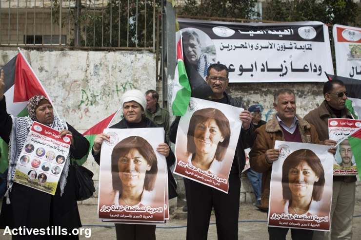 Protesters hold photos of feminist Palestinian member of parliament Khalida Jarrar, who is imprisoned by Israel on charges of incitement relating to her work as an elected official, outside the Ofer Military Prison, West Bank, April 16, 2015.