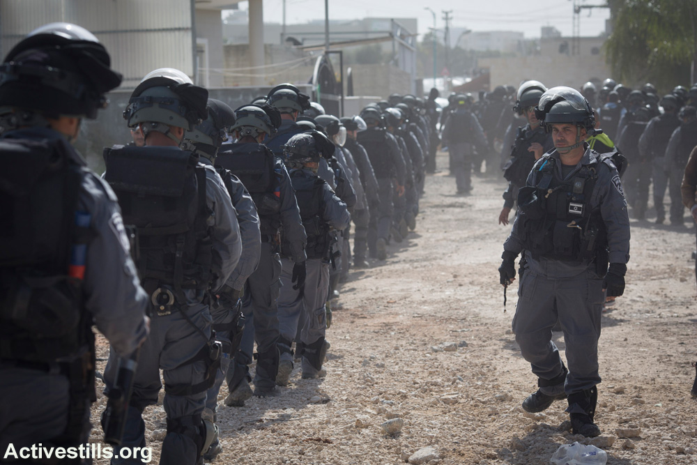 Israeli riot police march toward the site of a slated home demolition in Lod. Hundreds of police were sent to carry out the demolition of the home, in which a Palestinian citizen of Israel and her family lived, March 10, 2015. (Activestills.org)