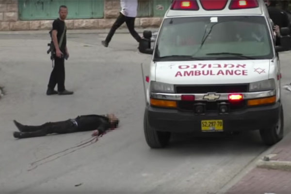 A Magen David Adom ambulance attempts to navigate around the body of a Palestinian man who shot in the head by an Israeli soldier in the occupied city of Hebron. The man, who reportedly took part in stabbing another soldier, had already been shot and incapacitated. March 24, 2016. (Screenshot/B'Tselem)