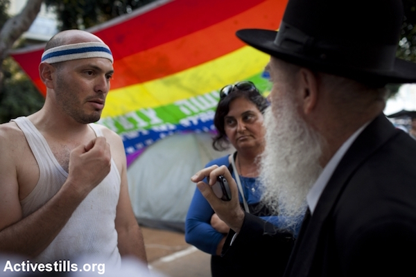 An ultra-Orthodox Jewish man argues with a secular social justice protester in Tel Aviv, July 18, 2011. (Oren Ziv/Activestills.org)