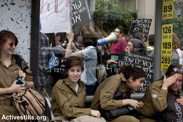 Soldiers watch the Slut Walk rally from a cafe, Tel Aviv, Israel, April 5, 2013. Protesters shouted slogans condemning discrimination against women based on their choice of dress or appearance. (Keren Manor/Activestills.org)