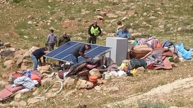 Employees of the Israeli Army's Civil Administration confiscate donated solar panels in Khirbet Jenbah in the southern West Bank, March 22, 2016. (Nasser Nawaj'a, B'Tselem)