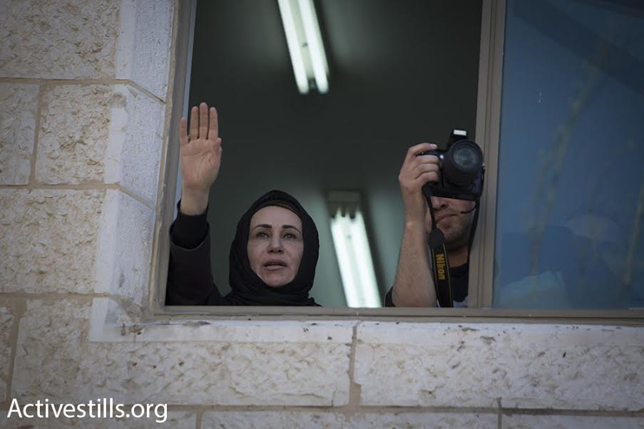 Palestinian MP Najat Abu Bakr waves at protesters from the Palestinian Legislative Council. Abu Bakr threw her support behind the strike and threatened to expose corruption in the Palestinian Authority, forcing her to remain in the PLC to avoid arrest. (photo: Oren Ziv/Activestills.org)