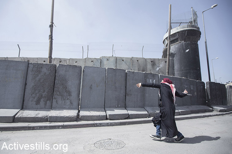 A Palestinian woman throws stones during a protest against the occupation a day before the International Women Day in front of Qalandiya military checkpoint, West Bank, March 7, 2015. The annual march was repressed by the Israeli army. (Activestills.org)