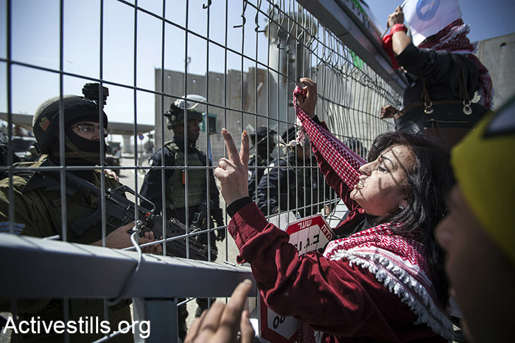 Palestinian women shout slogans during  the International Women Day protest in front of Qalandiya military checkpoint, West Bank, March 7, 2015. The annual march was repressed by the Israeli army.  (Activestills.org)