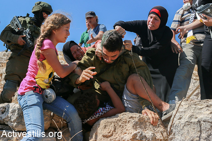 Members of the Tamimi family prevent from an Israeli solider from arresting Mohammed Tamimi, 11, during the weekly protest against the occupation in the West Bank village of Nabi Saleh, August 28, 2015.  (Activestills.org)