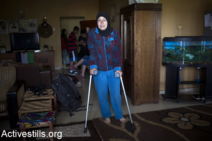 Nariman Tamimi, a prominent figure of the popular struggle in her village, is seen recovering at her home in Nabi Saleh, West Bank, April 3, 2015. Nariman was shot in the leg with a live bullet on November 22, 2014, by an Israeli soldier during the weekly protest against the occupation. She is still recovering for the injury.  (Activestills.org)