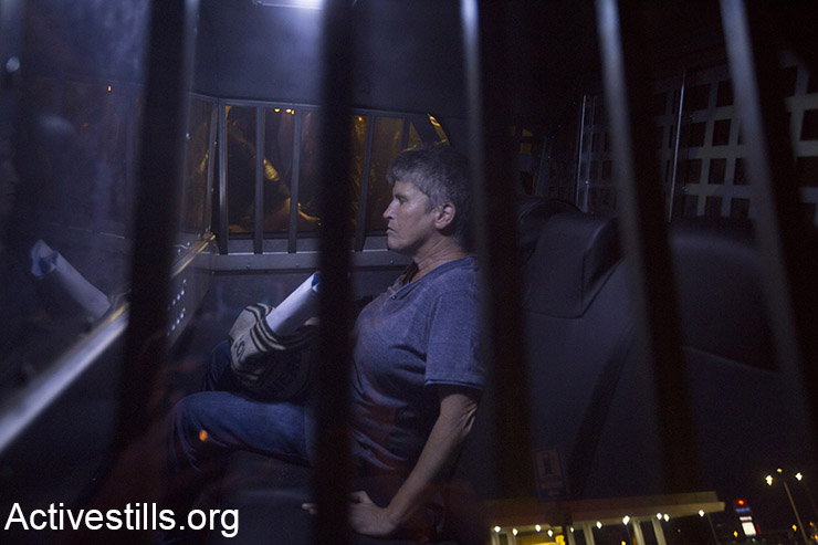 An Israeli activist, Zehava Greenfeld, sits inside a police car after she was arrested during a protest for the release of Palestinian Mohammed Allan, who is held by Israel without trial and who has slipped into a coma after a nearly two-month hunger strike, in the city of Ashkelon, August 16, 2015. Police prevented from Palestinian and Israel activists to arrive to the hospital in which Allan is held, arresting eight activists, using pepper spray and skunk water canon.  (Activestills.org)
