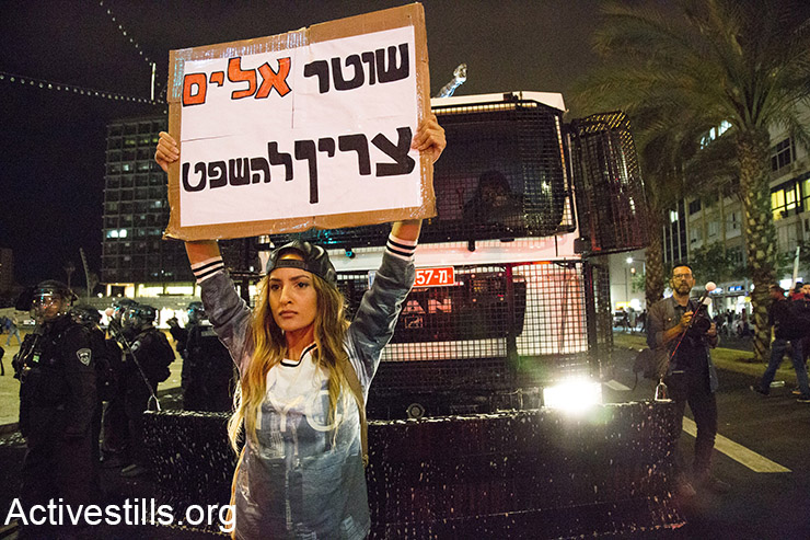 A protesters stand in front of a Police water canon during an Israeli Ethiopian protest against police brutality and racism, in Rabin square, Tel Aviv, May 3, 2015.  (Activestills.org)