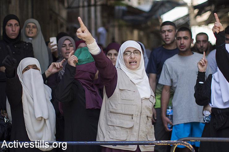 Palestinian women shout slogans as Israeli police forces block Palestinians at an entrance of the Al-Aqsa mosque compound in Jerusalem's old city, after Israeli police and authorities limited access to one of Islam's holiest sites, July 26, 2015, following clashes inside the compound.  (Activestills.org)