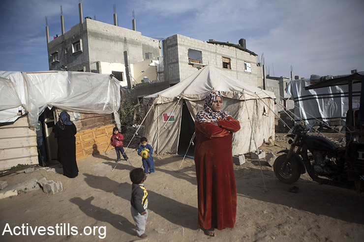 Members of the family of Wael al-Najjar in front of their makeshift shelter in the village of Khuza'a, East of Gaza Strip, February 14, 2015. Wael al-Najjar, who live in the makeshift shelter with his wife and 8 childre had to borrow around 500 USD to build the structure, and the family relies on neighbours, relatives and donations for their daily food. Khuzaa'a was heavily attacked and damaged during last Israeli offensive. Parts of the village were occupied by Israeli soldiers and out of reach by the ambulances and the media during the offensive.  Six months after the ceasefire that ended the offensive, 100, 000 Palestinians are still displaced and many live in very dire conditions. Rebuilding materials are scarce as the Gaza Strip face restrictions imposed by Israel.  (Activestills.org)