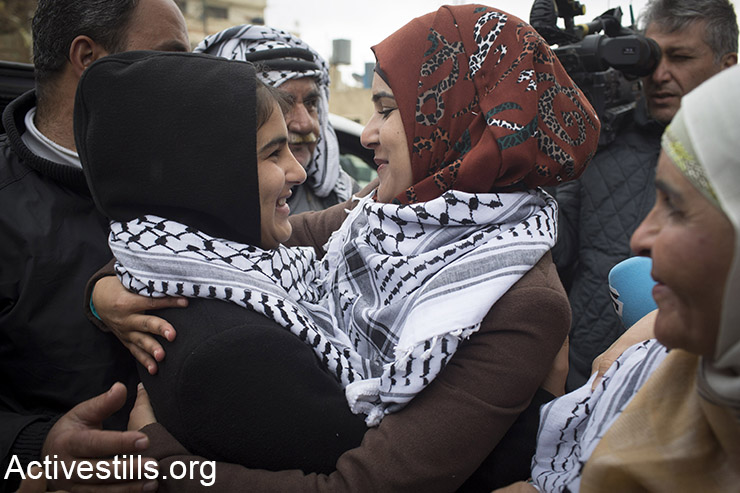 Palestinian Malak Al-Khateb, 14, is welcomed by family members, as she arrives to Beitin village near Ramallah, after being released from an Israeli prison, February 13, 2015. Al-Khateb, from Beitin village near Ramallah, was taken prisoner on December 31, 2014, and was subjected to interrogation and harsh treatment without legal representation. She had been accused of throwing stones at Israeli soldiers. On January 22, she was sentenced for two months in prison and a family was fined with 6,000 shekels fine ($1523). By the end of 2014, there were 197 children still imprisoned by Israel. (Activestills.org)