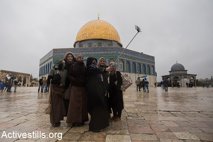 Palestinian women use their cell phone to photograph themselves outside Al Aqsa mosque in Jerusalem's old city, January 9, 2015.  (Activestills.org)