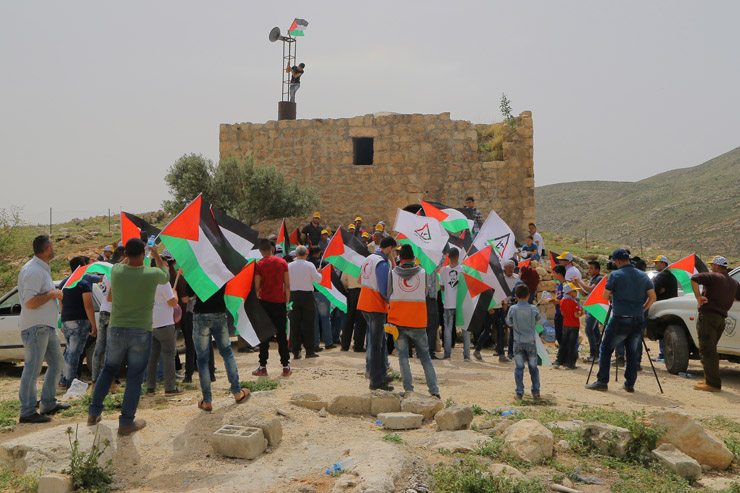 Dozens of Palestinians protest in solidarity with the residents of Khirbet Tana, where the Israeli army this week demolished structures for the fourth time in 2016, Khirbet Tana, April 8, 2016. (Ahmad al-Bazz / Activestills.org)