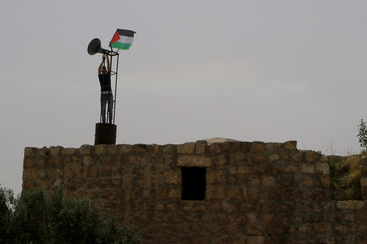 A man raises a Palestinian flag on top of the partially demolished Ottoman-era mosque in Khirbet Tana ahead of a protest against Israel's stepped up wave of demolitions, April 8, 2016. (Ahmad al-Bazz / Activestills.org)