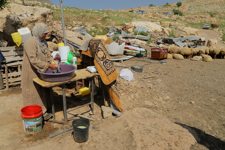 A woman washes clothes outside amid scattered belongings after Israeli military forces demolished several structures in Khirbet Tana, West Bank, April 7, 2016. (Ahmad al-Bazz / Activestills.org)