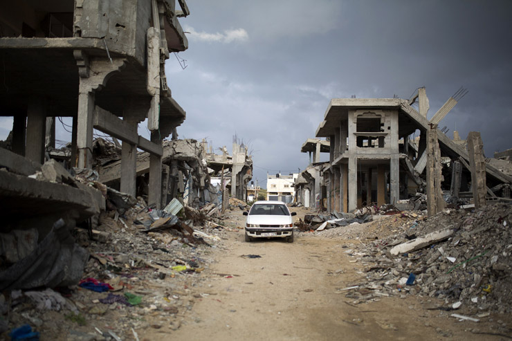 Palestinians drive through a destroyed quarter of Al Shaaf area in Al Tuffah, east of Gaza City, March 21, 2015. The rubble from destroyed apartment buildings is often recycled into low-quality cement. (Anne Paq/Activestills.org)