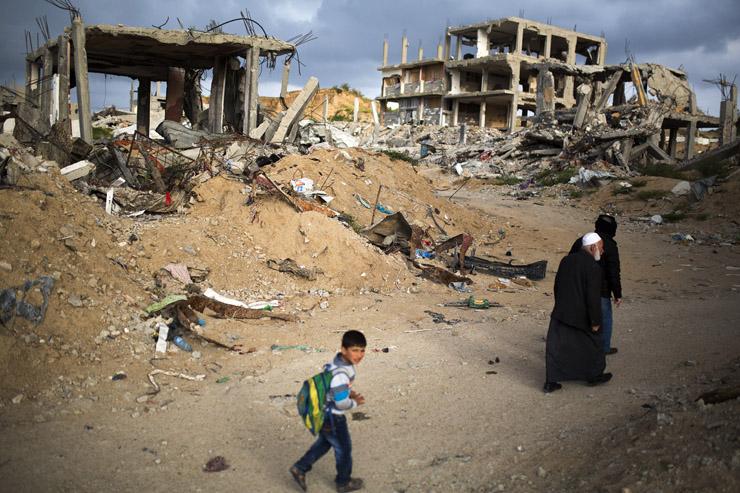 A family walks through a destroyed quarter of Al Shaaf area in Al Tuffah, east of Gaza City, March 21, 2015. (Anne Paq/Activestills.org)
