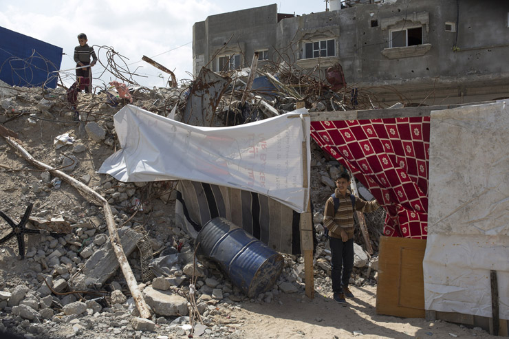 Children of the Abu Darouj family walk near the ruins of their destroyed home in the village of Zawaydeh, Gaza Strip, March 17, 2015. Five members of the family were killed during the 2014 war, including two children. (Anne Paq/Activestills.org)