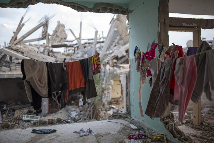 Clothes are hung in a half destroyed home in Al Tuffah, east of Gaza City, March 21, 2015. (Anne Paq/Activestills.org)