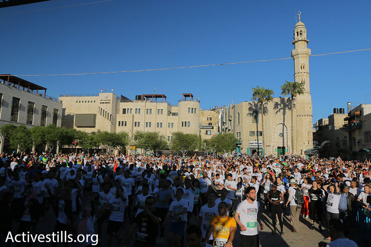 Runners in the 2016 Palestine Marathon gather in Manger Square outside the Church of the Nativity, Bethlehem, West Bank, April 1, 2016. (Ahmad al-Bazz/Activestills.org)