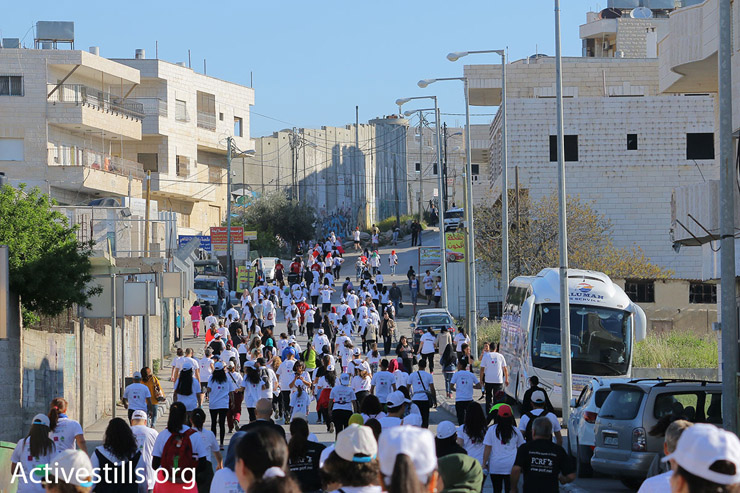 Runners in the 2016 Palestine Marathon with Israel's concrete separation wall in the background, Bethlehem, West Bank, April 1, 2016. (Ahmad al-Bazz/Activestills.org)