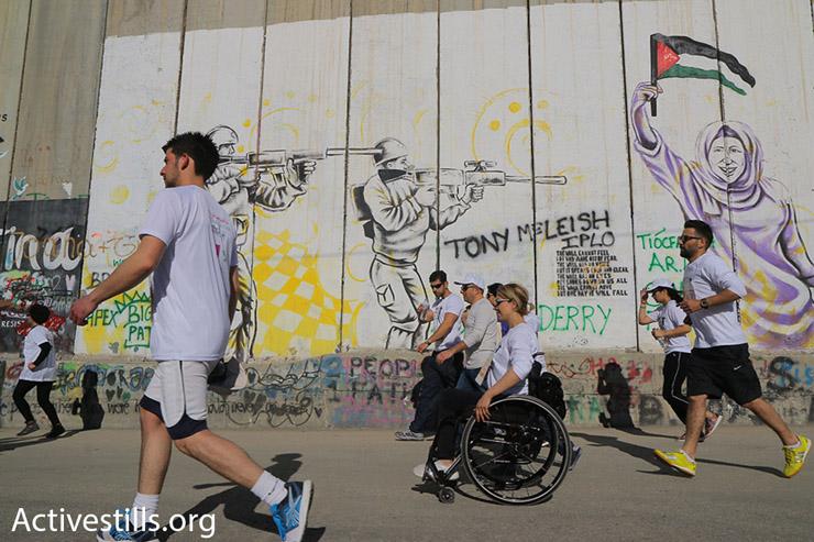 Participants in the 2016 Palestine Marathon run along Israel's concrete separation wall, Bethlehem, West Bank, April 1, 2016. (Ahmad al-Bazz/Activestills.org)