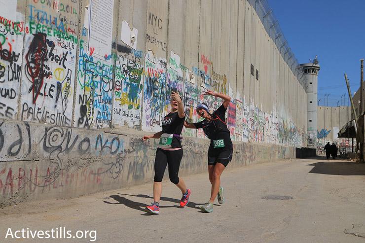 Two participants in the 2016 Palestine Marathon take a selfie along Israel's concrete separation wall, Bethlehem, West Bank, April 1, 2016. (Ahmad al-Bazz/Activestills.org)